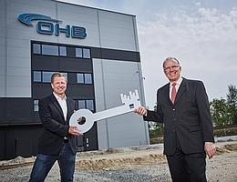 Mission accomplished: Architekt Arne Schlichtmann übergibt den symbolischen Schlüssel an Marco Fuchs, den Vorstandsvorsitzenden von OHB (v. l.). Damit nimmt OHB offiziell den größten Reinraum der Unternehmensgruppe in Betrieb. (Bild: OHB)