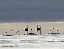 Die erste Station des Radio-Neutrino-Observatoriums auf dem grönländischen Eis. Die roten Fahnen markieren unterirdische Antennen, die von Solarmodulen (dunkle Rechtecke) mit Strom versorgt werden. (Bild: RNO-G, Cosmin Deaconu)