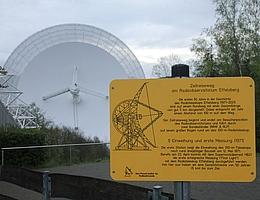 Der Zeitreiseweg am Radioteleskop Effelsberg beginnt am Besucherpavillon. Das Bild zeigt Station Nr. 1 (Einweihung und erste Messung 1971) vor dem Eingang des Pavillons und im Hintergrund das 100-m-Radioteleskop. (Bild: Norbert Junkes/MPIfR)